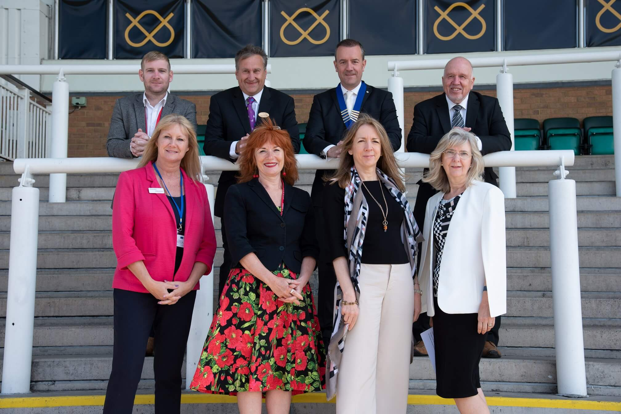 Four men and four woman standing on steps at Uttoxeter Racecourse at Let's Do Business event