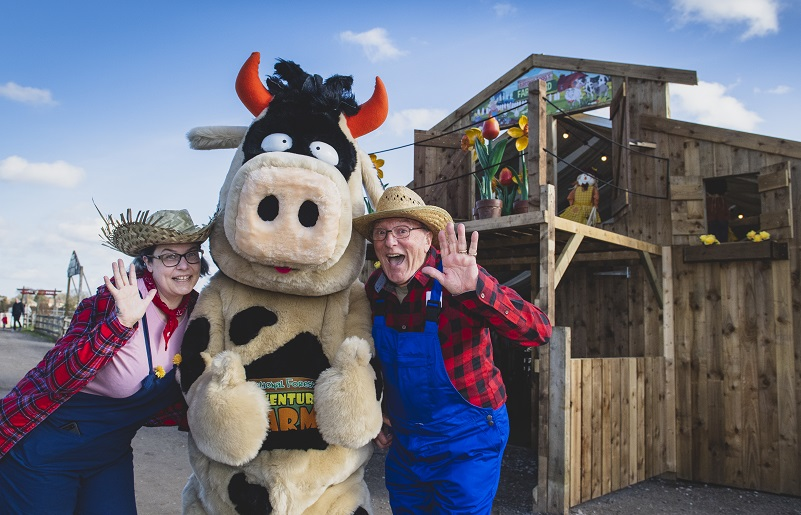 Crumpet the cow sticking his thumbs up as she helps two farmers with his chores