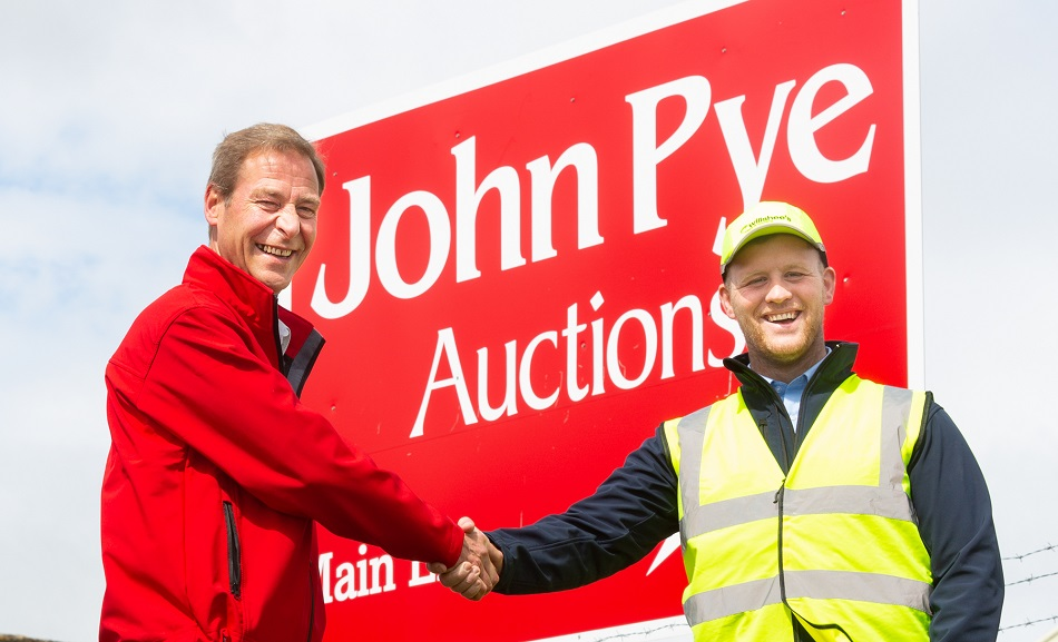 Two men shaking hands in front of a large sign to celebrate a business partnership
