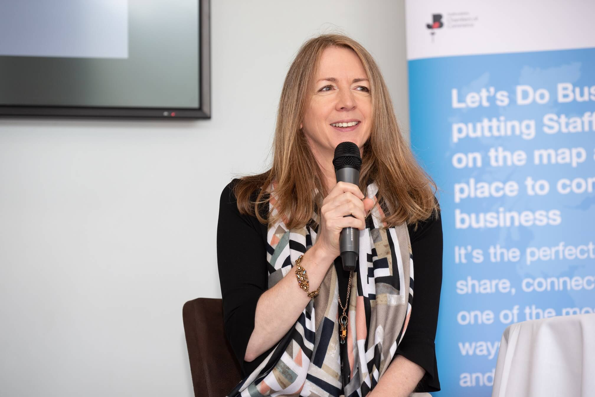 Business entrepreneur Rachel Elnaugh speaking into a microphone at Let's Do Business event on stage