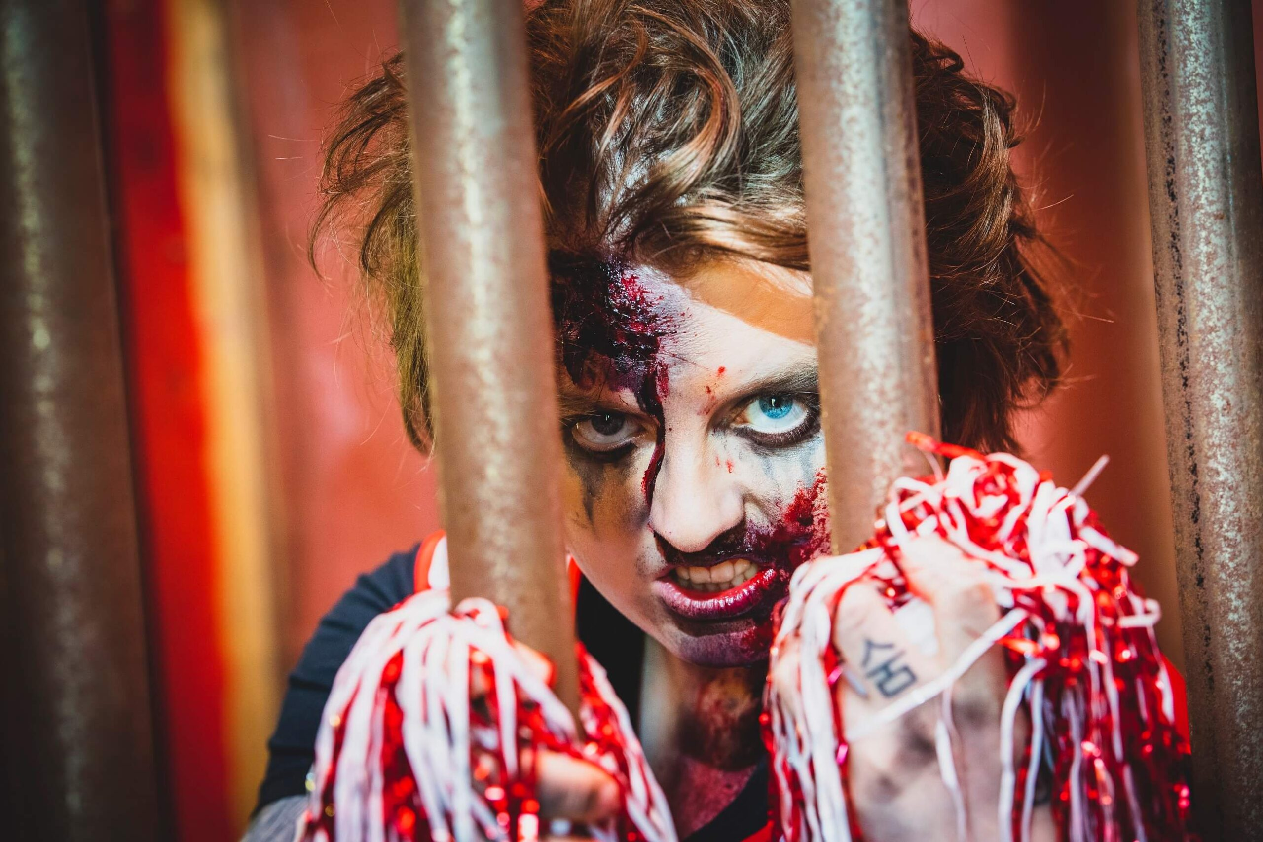 Zombie cheerleader holding onto the bars of a cage with blood on her face