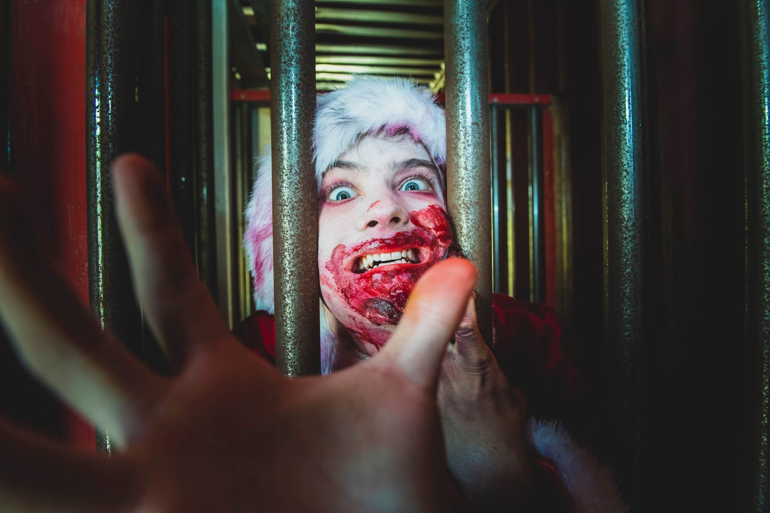 Zombie Santa reaching out from his cage with blood around his mouth