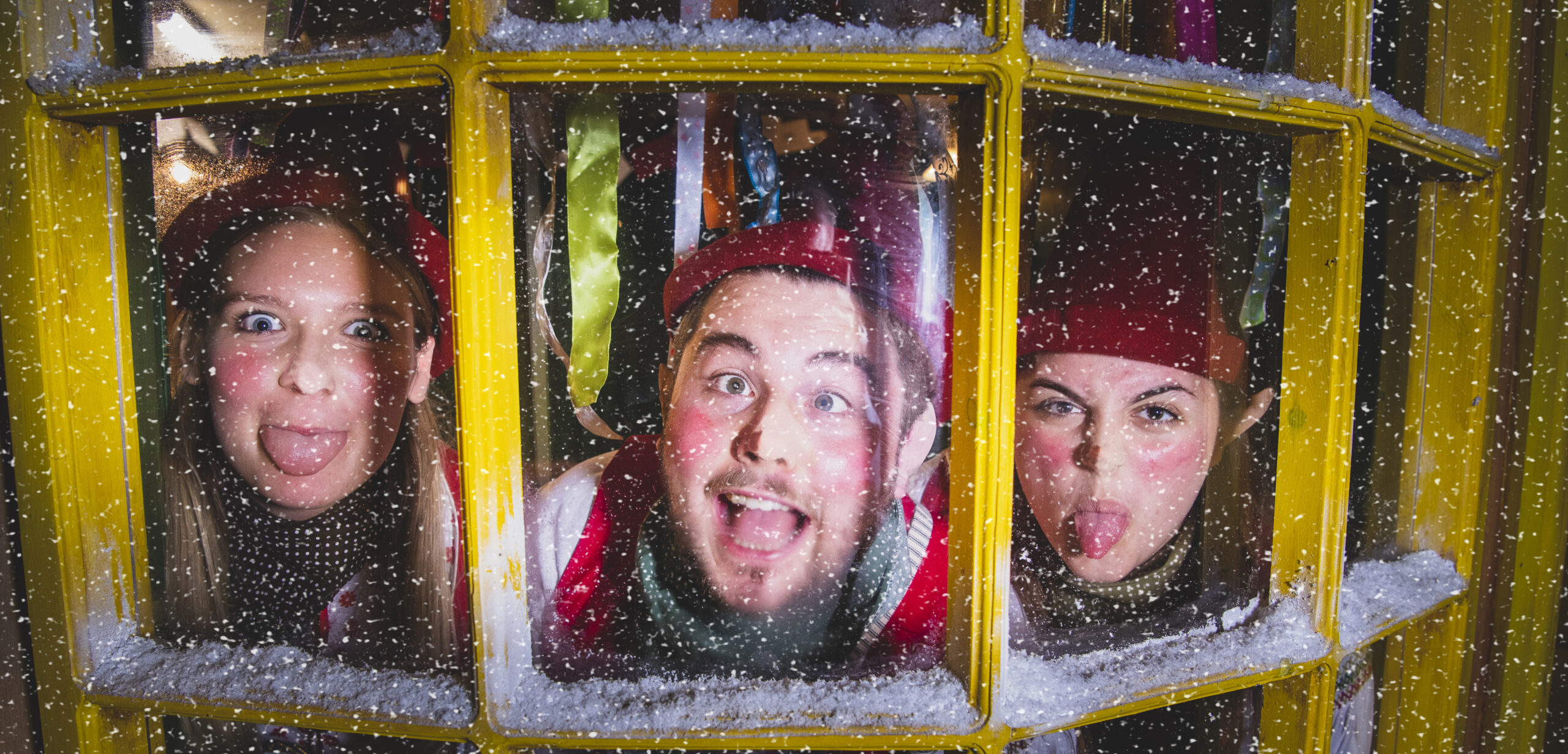 Three of Father Christmas' elves sticking their tongues out through a shop window
