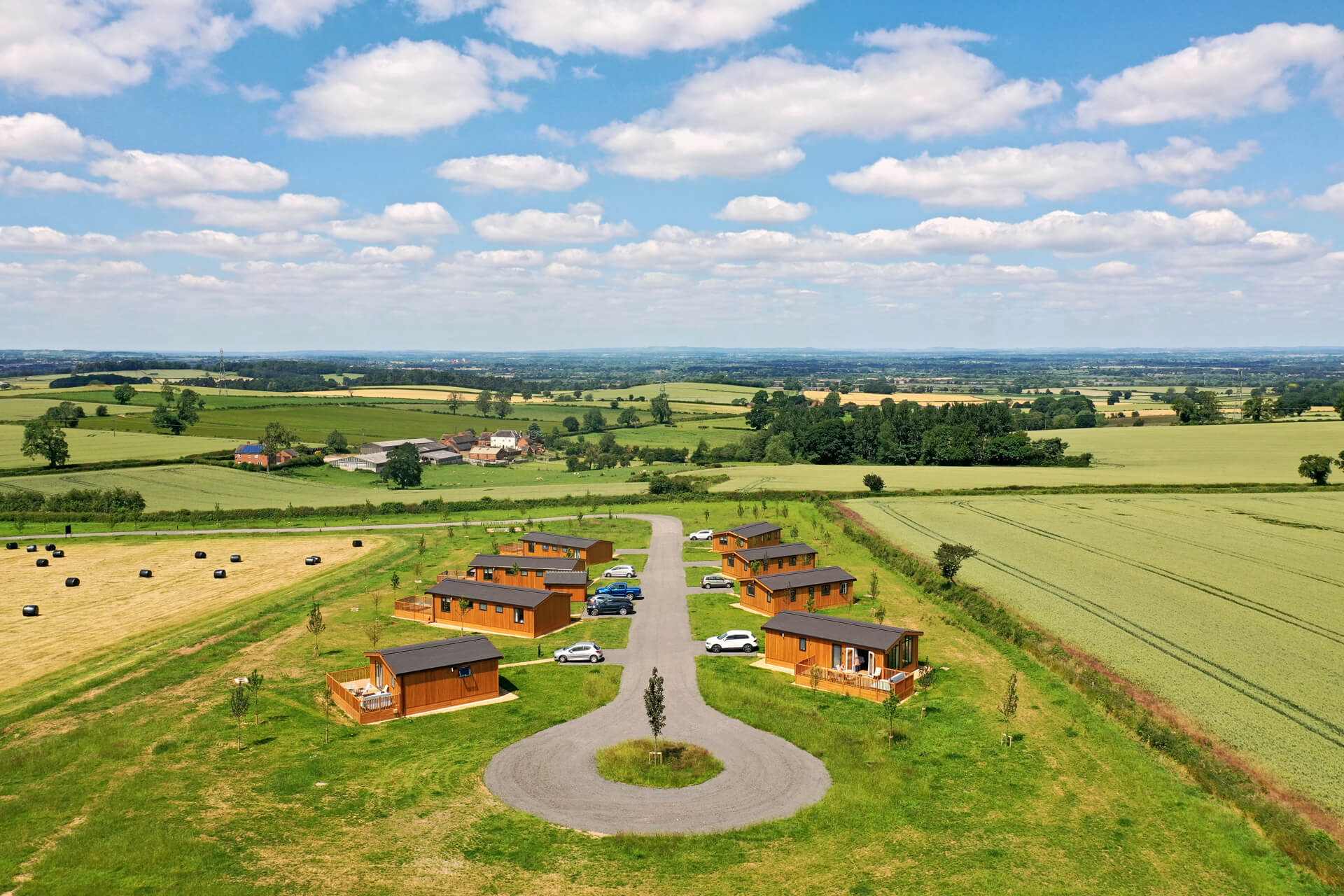 Aerial view of eight wooden lodges at the Knights Lodges of Bretby holiday park