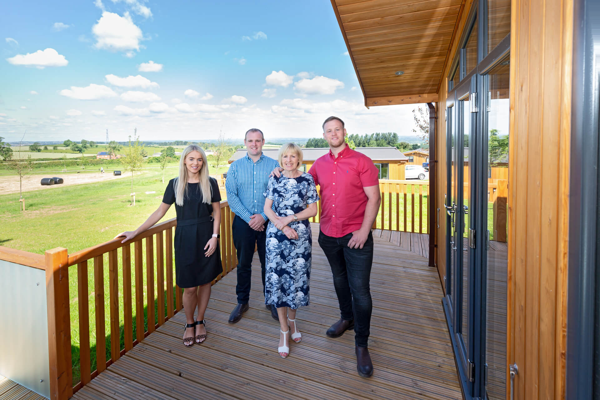 Four members of the Willshee family standing on the deck of one of their holiday lodges at the Knights Lodges of Bretby