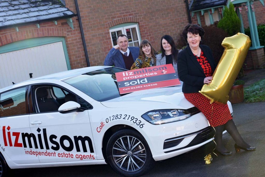 Liz Milsom and her three members of staff with a branded company car, outside their office