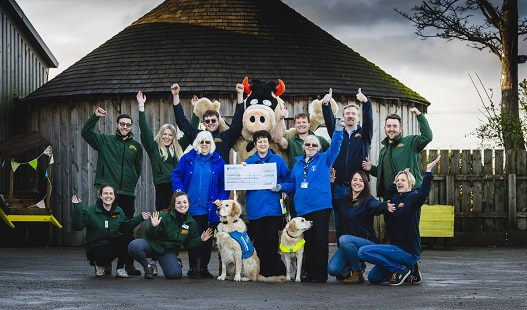 Ten members of staff at farm present donation cheque to three ladies from Guide Dogs charity with two guide dogs