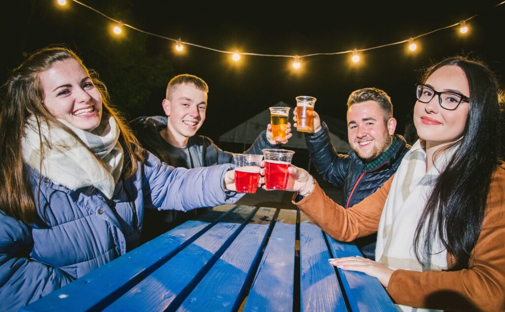 Four people enjoying a beer outdoors at the Moonlight Harvest event 2020