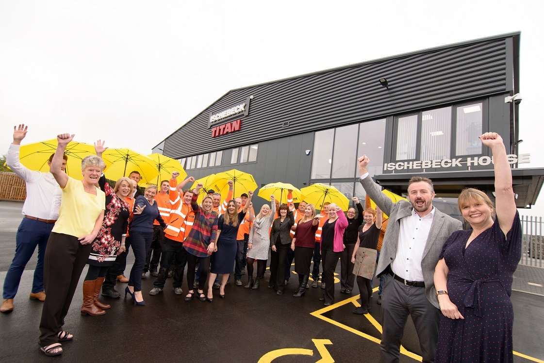 Twenty four people waving at new HQ office with yellow umbrellas
