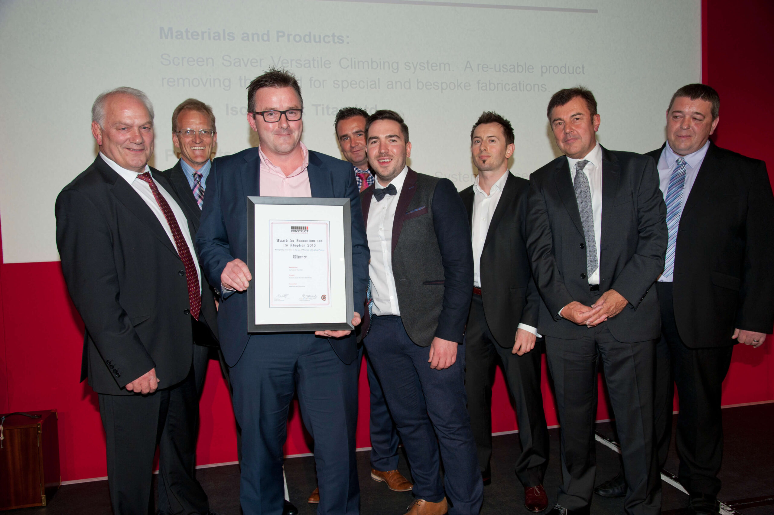 Eight men at CSG Awards event in suits, celebrating innovation award win
