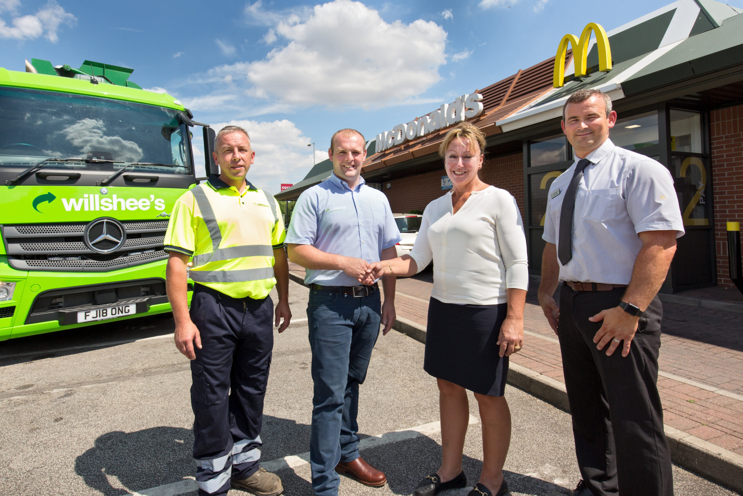 four people in front of waste lorry and McDonalds restaurant in Burton on Trent