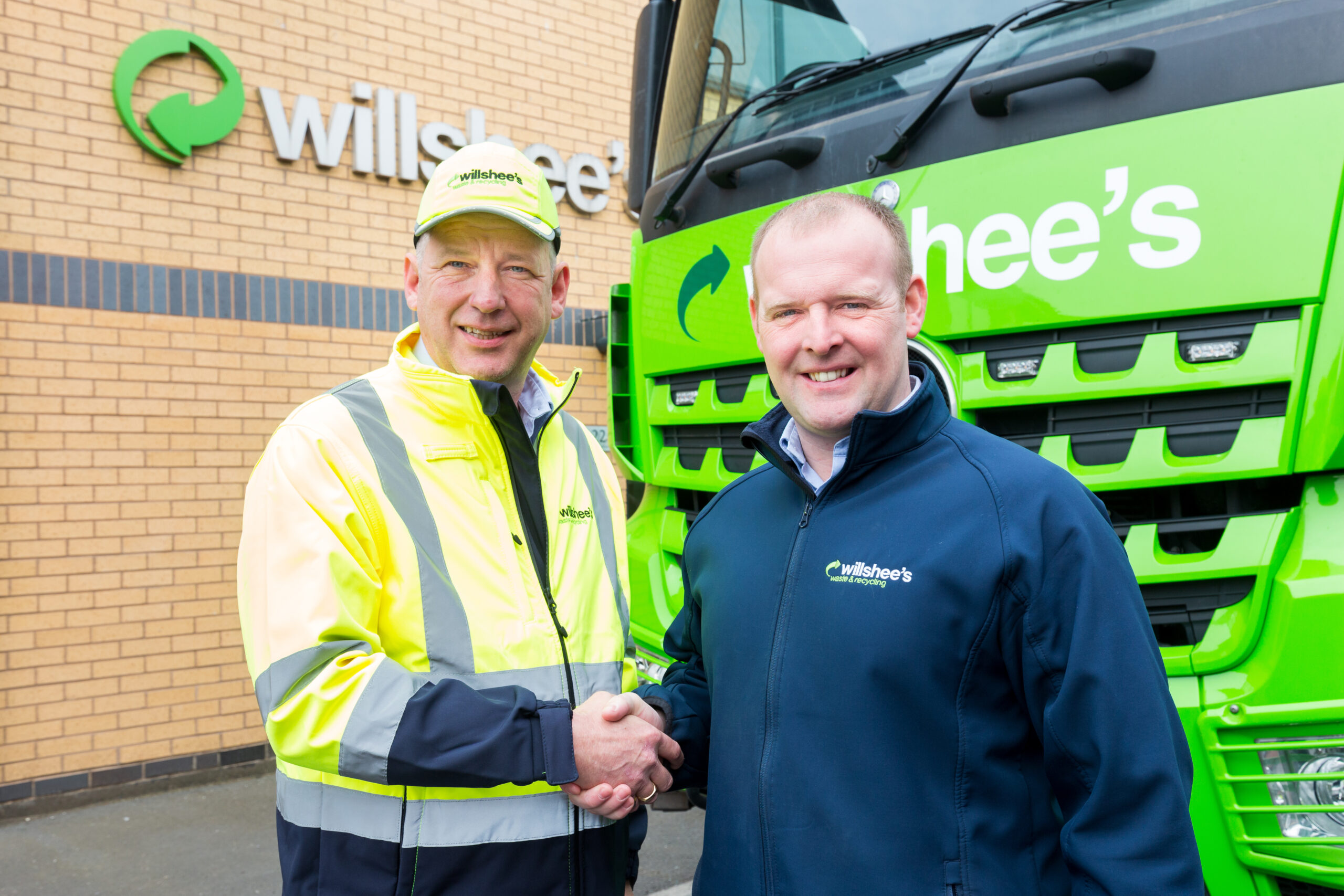 Gary Frost standing in front of recycling lorry with Dean Willshee - shaking hands